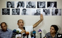 FILE - In this Wednesday, June 22, 2016 file photo, Egyptian lawyer and former presidential candidate Khaled Ali points to photos of jailed activists, who were arrested during protests over two disputed Red Sea islands, including Egyptian rights lawyer Malek Adly, top row third right, during a press conference, in Cairo, Egypt. An Egyptian court has ordered on Thursday, Aug. 25, 2016 the release of the prominent rights lawyer held in solitary confinement for the past three months after he challenged in court a decision by the country's president to hand over two Red Sea islands to Saudi Arabia.