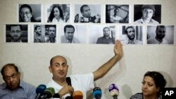 FILE - Egyptian lawyer and former presidential candidate Khaled Ali points to photos of jailed activists who were arrested during protests over two disputed Red Sea islands, June 22, 2016.