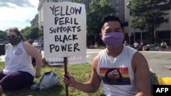 """一名亞裔美國人手舉""""黑人的命也是命""""的標語牌"""