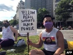 """Viet Hoai Tran, 27 t, cầm biểu ngữ """"Hiểm họa Da vàng hậu thuẫn Sức mạnh cho người Da đen"""" ngày 15/6/2020 tại thủ đô Washington. (AFP)"""