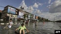 Một phụ nữ Thái, ngồi trên chiếc phao, và các cư dân khác đang rời khỏi khu vực đã bị lụt trong thủ đô Bangkok, Thailand hôm 26/10/11