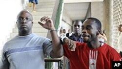 Theophile Kouamouo, le directeur des rédactions du Nouveau Courrier (à gauche), et le rédacteur en chef, Saint-Claver Oula (à droite) au palais de justice d'Abidjan
