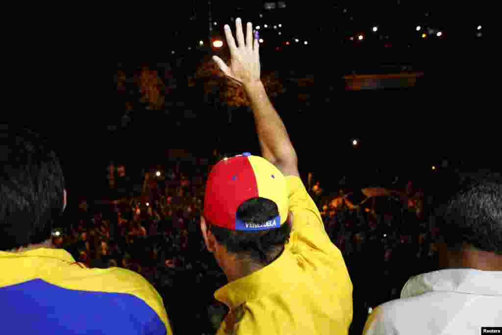 Venezuela's opposition leader Henrique Capriles waves to supporters after a news conference at his campaign headquarters in Caracas, April 15, 2013.