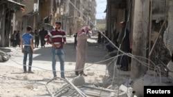 지난 11일 시리아 반군이 점령하고 있는 알레포 지역에 공습이 있은 후 주민들이 무너진 마을 터를 둘러보고 있다.