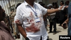 A hospital official wearing a blood stained shirt stands outside the hospital after an attack on a bus in Karachi, Pakistan, May 13, 2015.