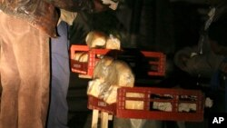 FILE: An unidentfied man buys a loaf of bread at night for 150 billion Zimbabwe dollars in Harare