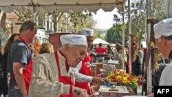 Актер Кирк Дуглас наполняет тарелки едой, как делает это каждый год в День Благодарения.