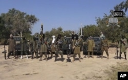 FILE - This file image taken from a video released, Oct. 31, 2014, by Boko Haram, shows Abubakar Shekau, center.