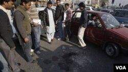 Warga di Lahore, Pakistan melihat tumpahan darah di lokasi insiden penembakan antara seorang diplomat AS dan dua penyerangnya, Kamis 27 Januari 2011.