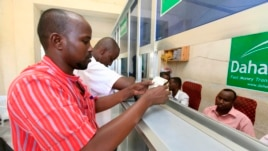 A Somali man collects his money at a Dahabshiil money transfer office in southern Mogadishu, May 8, 2013.