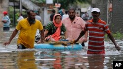 An elderly Sri Lankan woman is shifted on a makeshift raft at a flooded area in Colombo, Sri Lanka, Tuesday, May 17, 2016. The Disaster Management Center said that 114 homes have been destroyed and more than 137,000 people have been evacuated to safe locations as heavy rains continue. (AP Photo/Eranga Jayawardena)