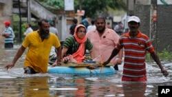 17일 스리랑카 콜롬보에서 주민들이 범람한 도로를 건너고 있다.