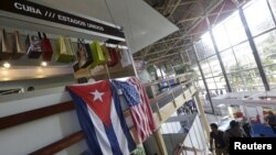 FILE - U.S. and Cuban flags hang side by side at the U.S pavilion during the Havana International Fair (FIHAV) in Cuba, Nov. 2, 2015.