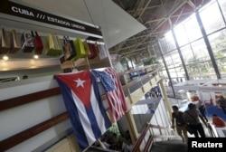 FILE - U.S. and Cuban flags hang on a wall at the U.S pavilion during the Havana International Fair, Havana, Cuba, Nov. 2, 2015.