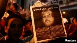 示威者手持遇刺身亡的布拉赫米的头像。2013年7月25日