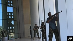 Rebel fighters take shelter as an intense gunbattle erupted outside the Corinthia hotel, where many foreign journalists are staying, in Tripoli, Libya, August 25, 2011
