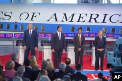 Republican presidential candidates, former New York Gov. George Pataki, left, former Pennsylvania Sen. Rick Santorum, second from left, Louisiana Gov. Bobby Jindal, second from right, and Sen. Lindsey Graham, R-S.C., take the stage in the early CNN Republ