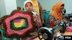 Warga anggota kelompok wirausaha Rumah Kreatif Kembang Melati di Surabaya memperlihatkan hasil kerjanya. (VOA/Petrus Riski)