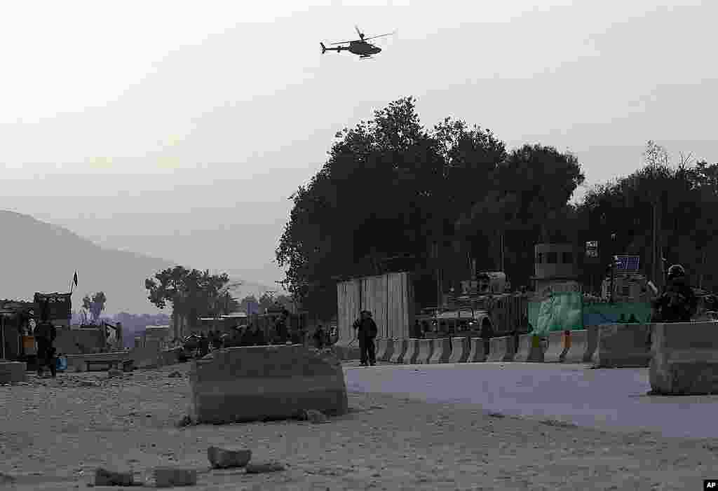 Afghan National Army soldiers keep watch as a NATO helicopter flies over the site of a car bomb attack in Jalalabad on February 27, 2012. (Reuters)