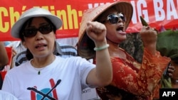 FILE - Bui Thi Minh Hang (R), 47, shouting anti-China slogans next to dissident lawyer Cu Huy Ha Vu's wife, Nguyen Thi Duong Ha (L), during an anti-China protest in downtown Hanoi.