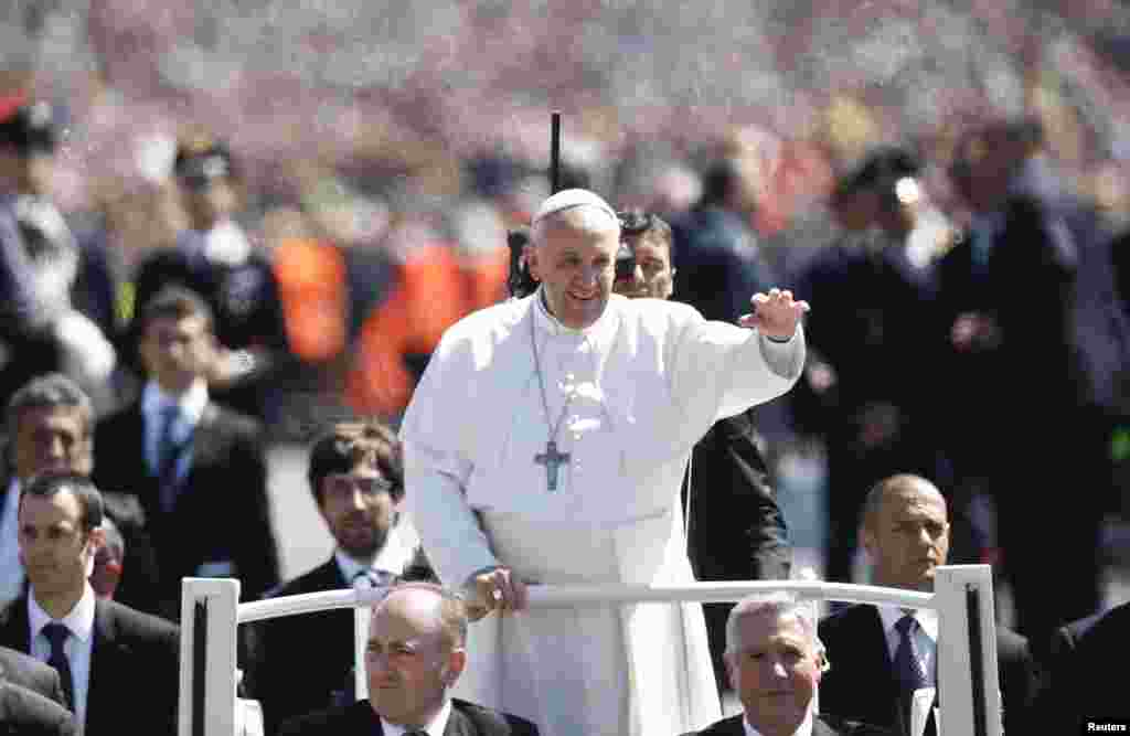 Pope Francis waves as he leads the Easter mass in Saint Peter's Square at the Vatican, April 20, 2014.
