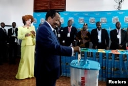 FILE - Cameroonian President Paul Biya casts his ballot while his wife Chantal Biya watches at a polling station during the presidential election in Yaounde, Cameroon, Oct. 7, 2018.