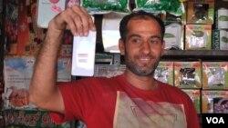 印度迈索尔一位集市摊主向记者展示他心爱的小米手机。(美国之音朱诺拍摄,2015年12月4日)