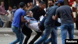 16일 이집트 카이로 람세스 광장에서 무르시 지지 시위 도중 다시 유혈 충돌이 벌어진 가운데, 시위대가 부상자를 옮기고 있다.
