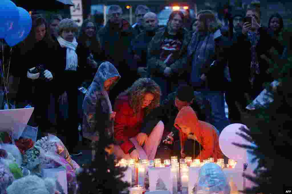 People gather at a memorial for victims near the school on the first Sunday following the mass shooting at Sandy Hook Elementary School on December 16, 2012 in Newtown, Connecticut.
