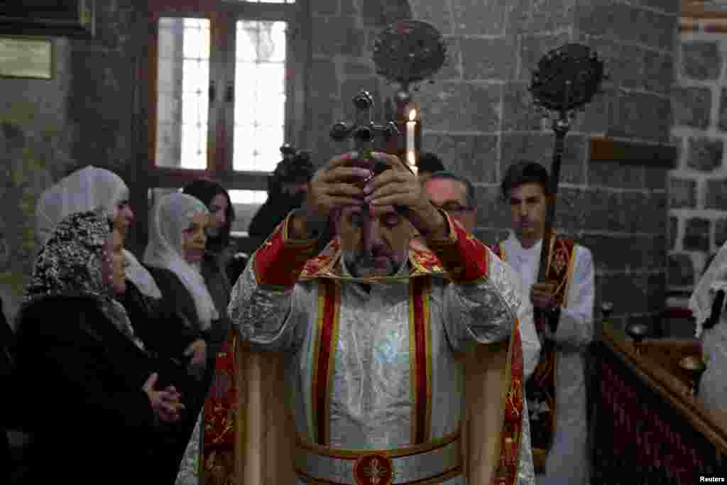 A Syrian Christian priest leads a mass on Christmas at the Virgin Mary Syriac Orthodox Church in Diyarbakir, Turkey, Dec. 25, 2018.