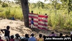 Des enfants regardent un spectacle de marionnettes qui vise à guérir les enfants déplacés qui ont été témoins d'atrocités dans le nord du Mozambique, dans un camp de déplacés à Metuge le 21 mai 2021.