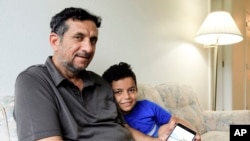 Hadi Mohammed sits with his 9 year old son Mohammed Ghaleb, as he displays a photo of his son as a baby in Baghdad, in their Lincoln, Neb. apartment. Sept. 29, 2018. Death threats drove Hadi Mohammed out of Iraq and to a small apartment in Nebraska, where he and his two young sons managed to settle as refugees. But the danger hasn't been enough to allow his wife to join them.