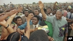 African National Congress President Nelson Mandela, right, waves to the gathered crowd at Jouberton Township stadium as people reach out to touch him during a campaign rally on Jan. 30, 1994.