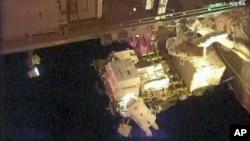 En esta imagen tomada de NASA Television, los astronautas Scott Kelly (parte superior derecha) y Kjell Lindgren (abajo) realizan trabajo de mantenimiento afuera de la Estación Espacial Internacional el 28 de octubre de 2015.