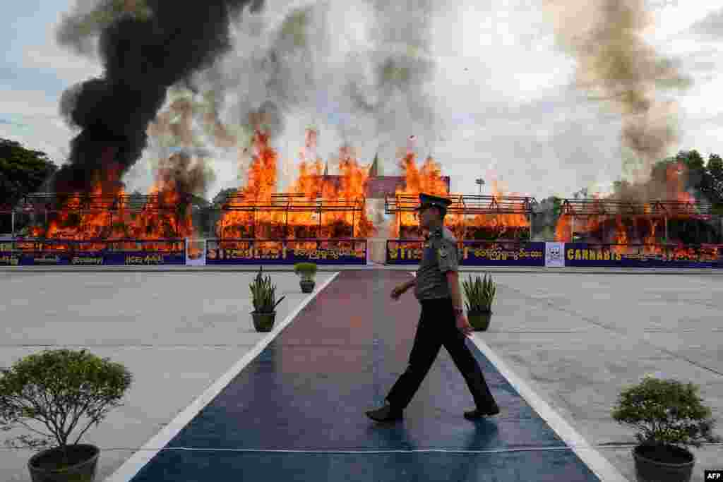 A police officer walks in front of a fire burning seized illegal drugs during a ceremony to mark the United Nations' International Day Against Drug Abuse and Illicit Trafficking in Yangon, Myanmar.
