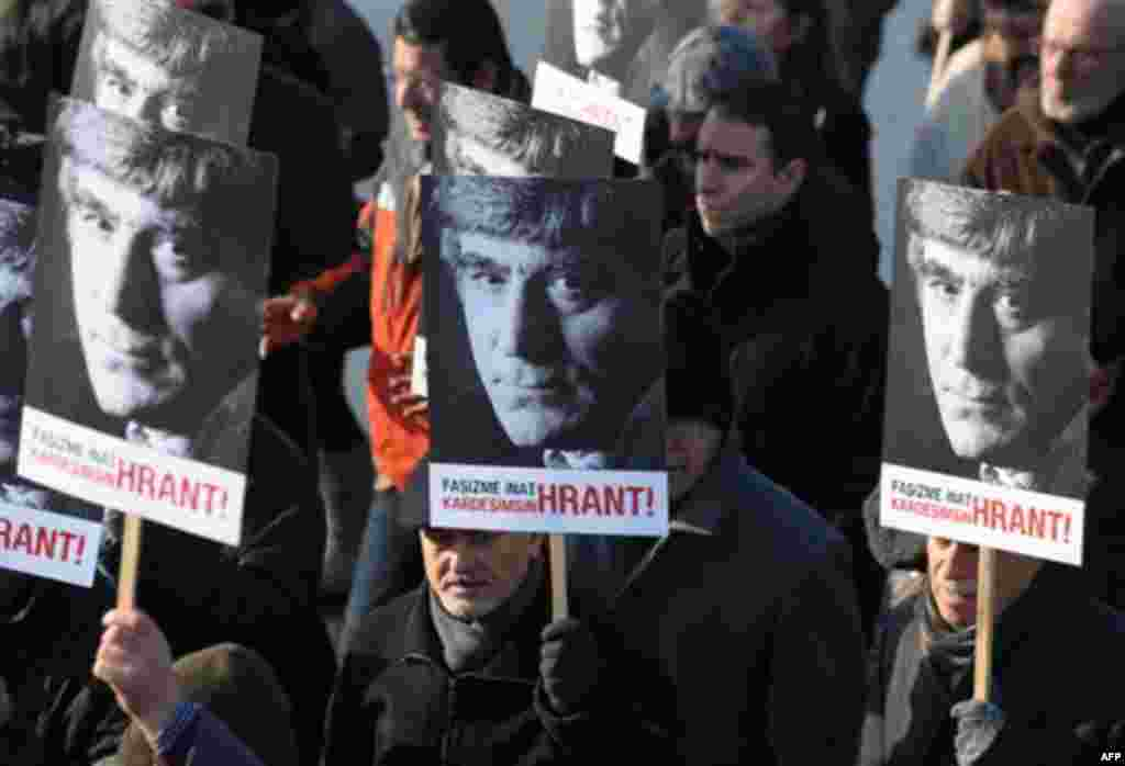 Hundreds of people hold placards that read 'you are my brother Hrant stubbornly against fascism' outside a courthouse in Istanbul, Turkey, Tuesday, Jan. 17, 2012. A prosecutor is demanding life imprisonment for seven men accused of involvement in the kil