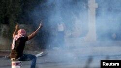 西岸城市拉马拉一名巴勒斯坦抗议者坐在用来盖住以色列催泪弹的桶上。(2015年10月15日)
