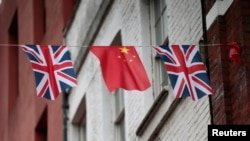 FILE - Chinese and British flags fly in London's Chinatown, Britain, Oct. 19, 2015.