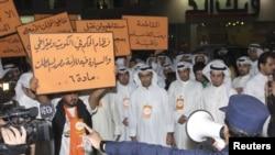 Seorang polisi memerintahkan para pengunjuk rasa untuk membubarkan diri dari depan sebuah kantor surat kabar di Shuwaikh, Kuwait (31/10). RIbuan warga berunjuk rasa menuntut dibebaskannya Musallam al-Barrack, seorang tokoh oposisi Kuwait yang ditahan atas tuduhan menghina raja, dua pekan lalu.