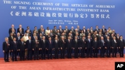 Delegates pose for a group photo at the signing ceremony for the Articles of Agreement of the Asian Infrastructure Investment Bank (AIIB) at the Great Hall of the People in Beijing, June 29, 2015.