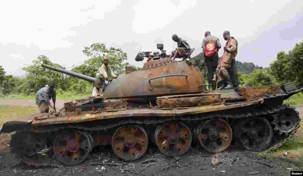 Anak-anak Kongo bermain tank yang ditinggalkan oleh para pemberontak M23 yang menyerah di kota Kibumba, Republik Demokratik Kongo.