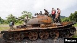 Des enfants jouant sur un tank abandonné par le M23