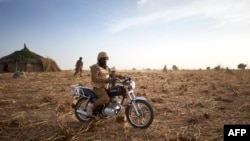 FILE - A soldier of the Burkina Faso Army sits on his motorcycle during a patrol in Burkina Faso, November 9, 2019. Two soldiers were killed by a homemade bomb in southeast Burkina Faso on October 11, 2021.