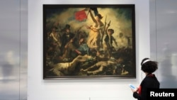 "A woman looks at Eugene Delacroix 's painting, ""Liberty Leading the People"" (28 July 1830) during media day on the eve of the inauguration of the Le Louvre Lens Museum, December 3, 2012."