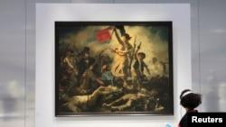 Une femme admire le tableau d'Eugène Delacroix, 'La Liberté guidant le peuple' (28 juillet 1830), à la Galerie du Temps au musée du Louvre-Lens dans le nord de la France, le 3 décembre 2012.