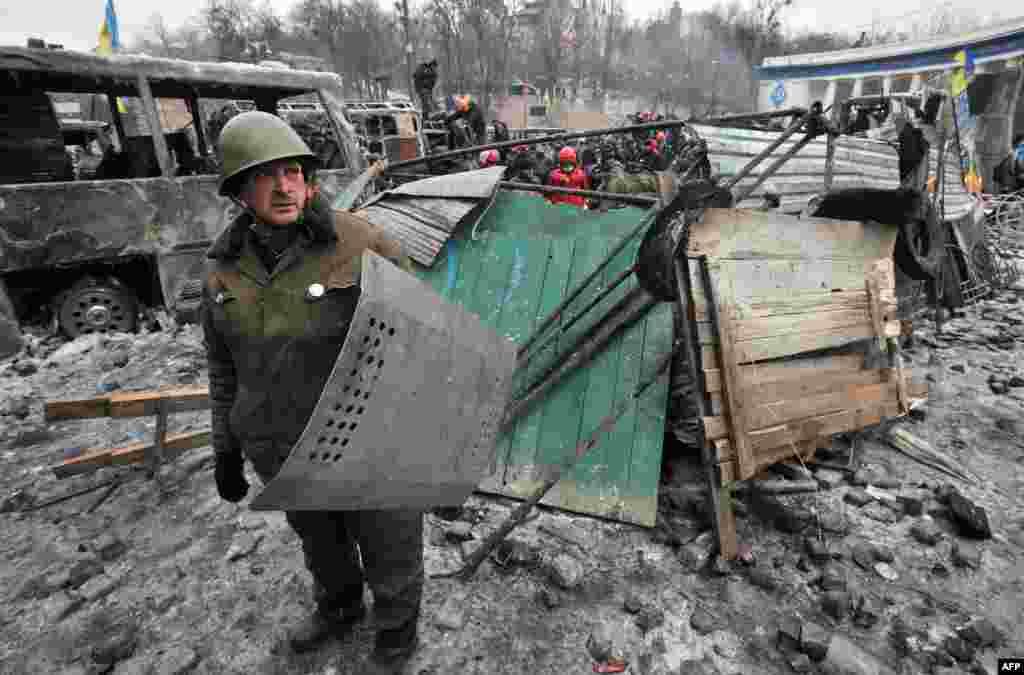 우크라이나 키예프에서 반정부 시위대가 진압 경찰과 충돌한 가운데, 시위대 일원이 경찰이 쓰던 방패를 손에 들고 있다.