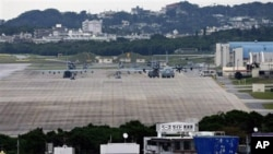 FILE - U.S military airplanes and helicopters sit on the airstrip at Futenma Marine Corps Air Station surrounded by houses in Ginowan, Okinawa, Japan.