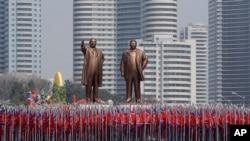 Sinh viên mang quốc kỳ và hai tượng đồng của lãnh đạo quá cố Kim Il Sung và Kim Jong Il trong cuộc diễu hành tại Bình Nhưỡng hôm 15/4