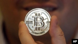 FILE - Mike Caldwell, a 35-year-old software engineer, holds a 25 Bitcoin token at his shop in Sandy, Utah.