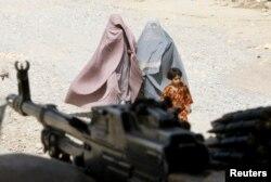 Perempuan Afghanistan berpakaian burqa dan seorang gadis berjalan melewati kantor polisi setempat di kota Kandahar, Afghanistan selatan, 22 Maret 2010. (REUTERS/Shamil Zhumatov)